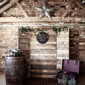 Styled photobooth backdrop with rustic palette wood stand and personalised signage