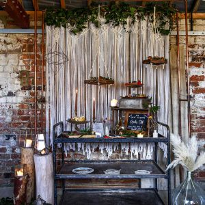 Industrial Trolley Cake Table, With Macrame Backdrop, Hanging Shelves and Candle Light